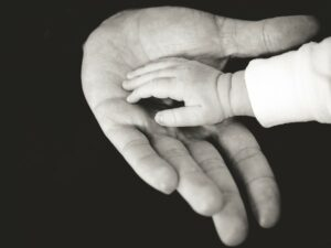baby hand in an adults hand.
